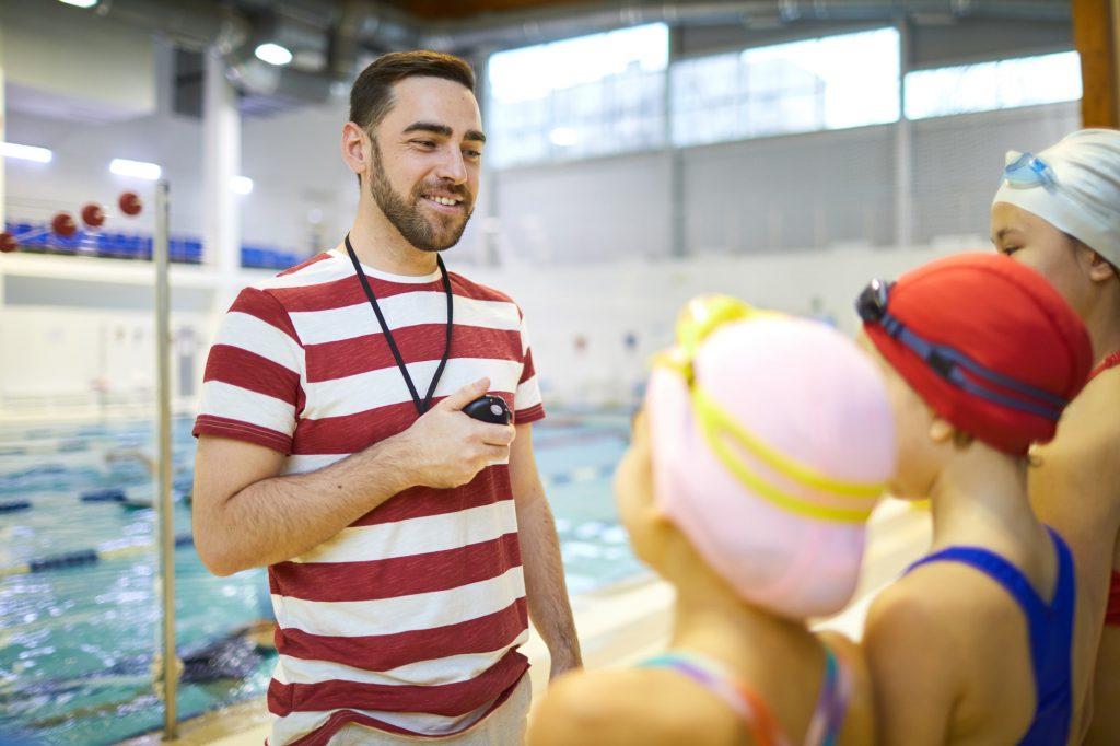 Swim trainer teaching children to swim