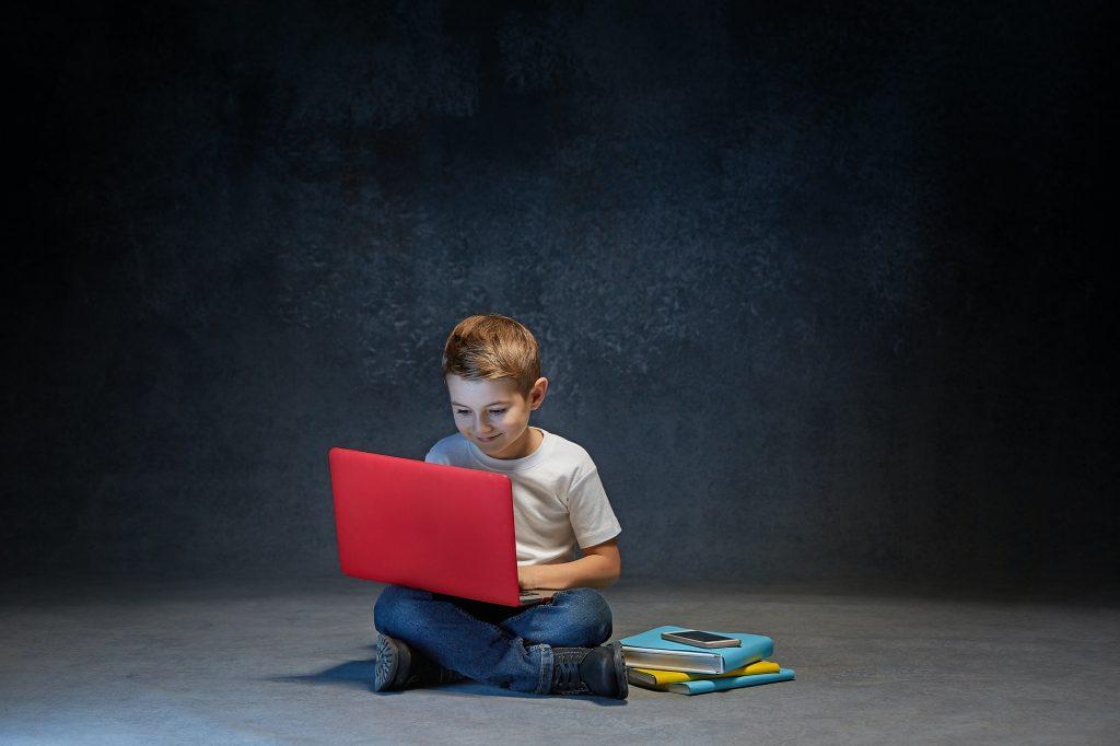 Little boy sitting with laptop in studio
